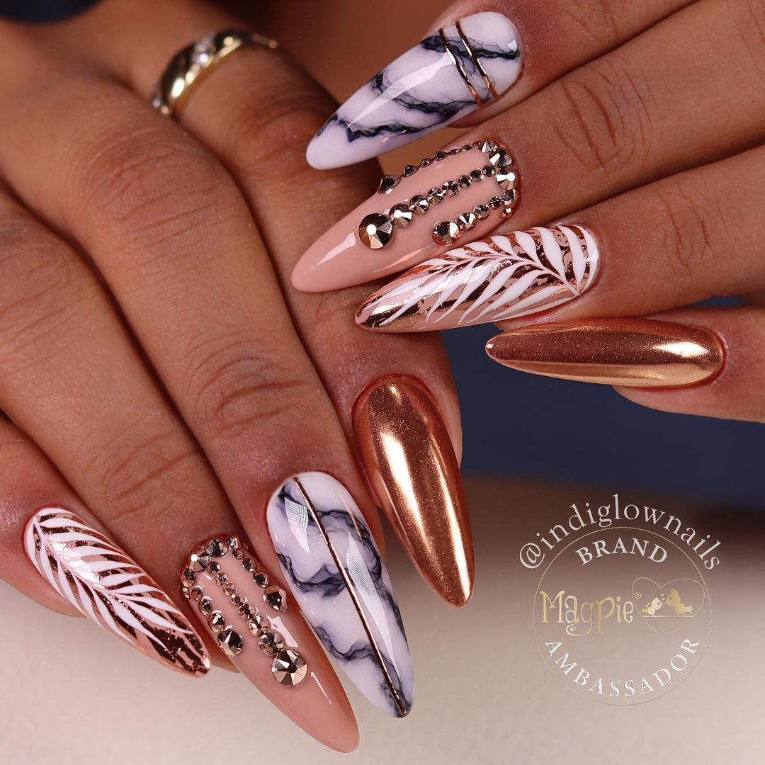 Rose gold chrome nails with marble texture and rhinestones