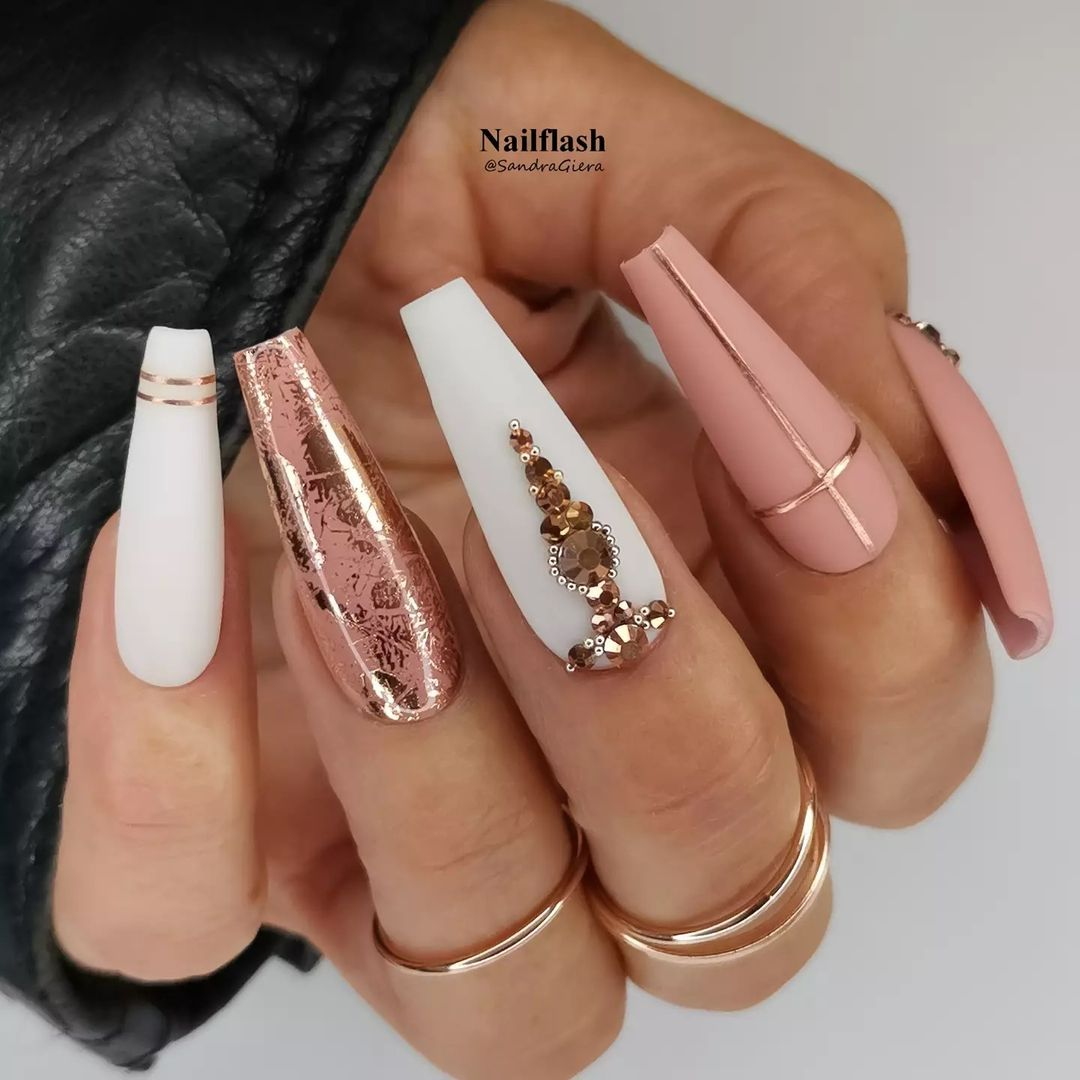 Rose gold nails with white polish and rhinestones