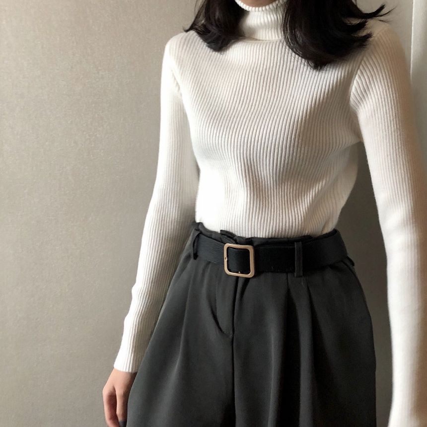 White turtleneck sweater with black trousers