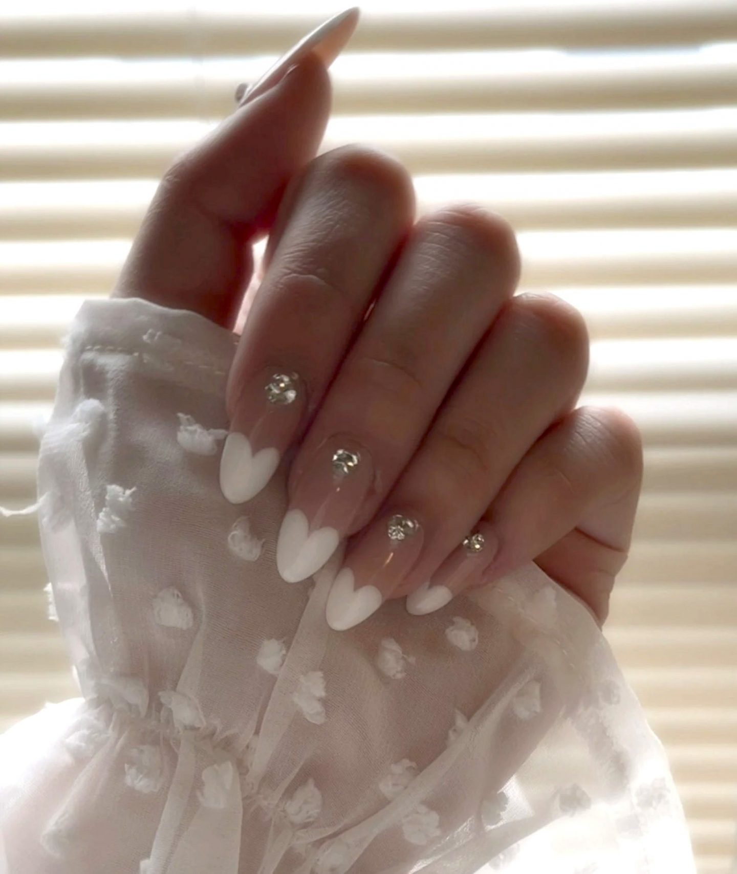 Cute French tip nails with white hearts and crystals