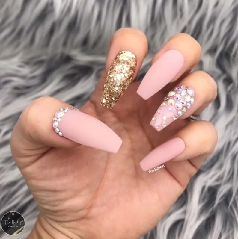 Matte pink coffin nails with gold glitter and rhinestones