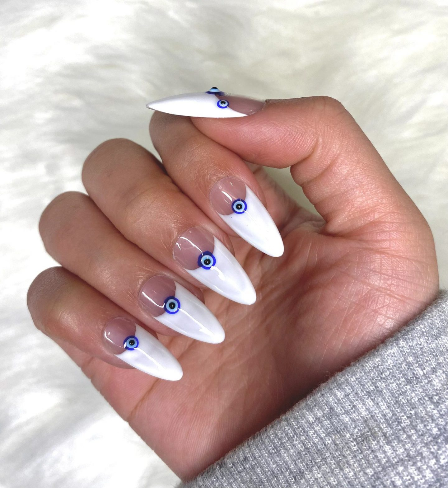 White French tip nails with evil eye in almond shape