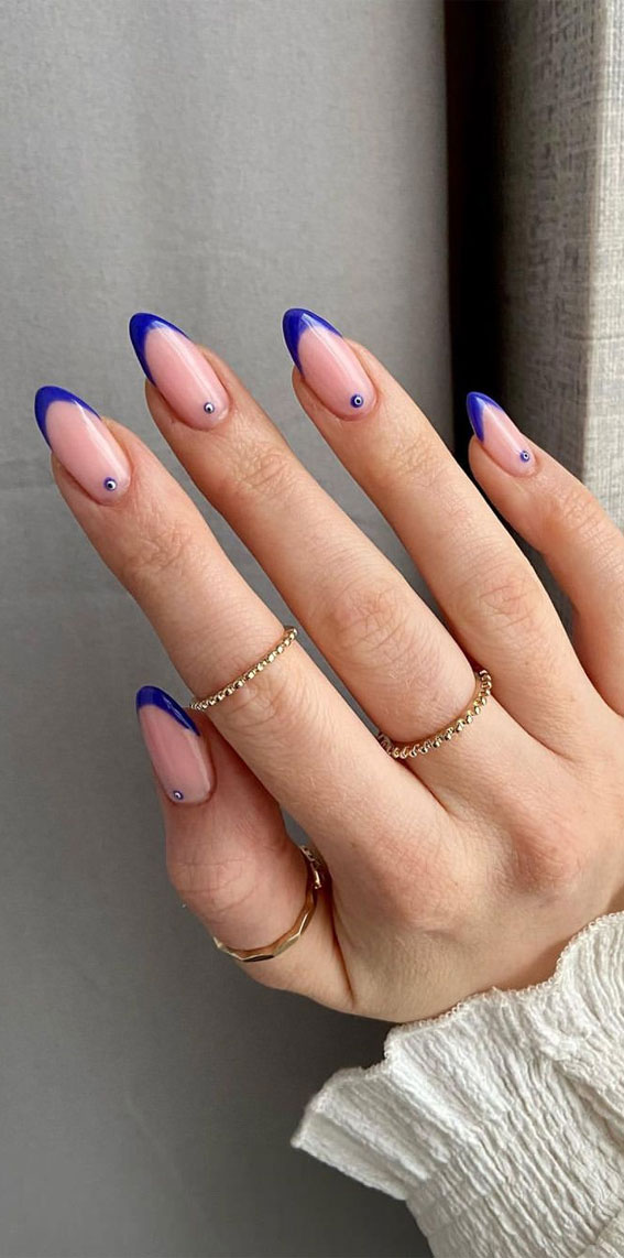 Blue French tip nails with evil eye nail art