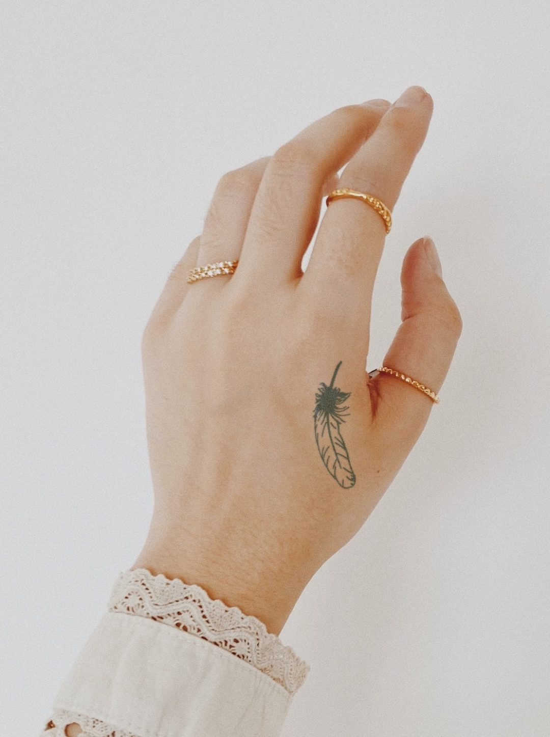 Cute dainty feather tattoo for fingers and hand