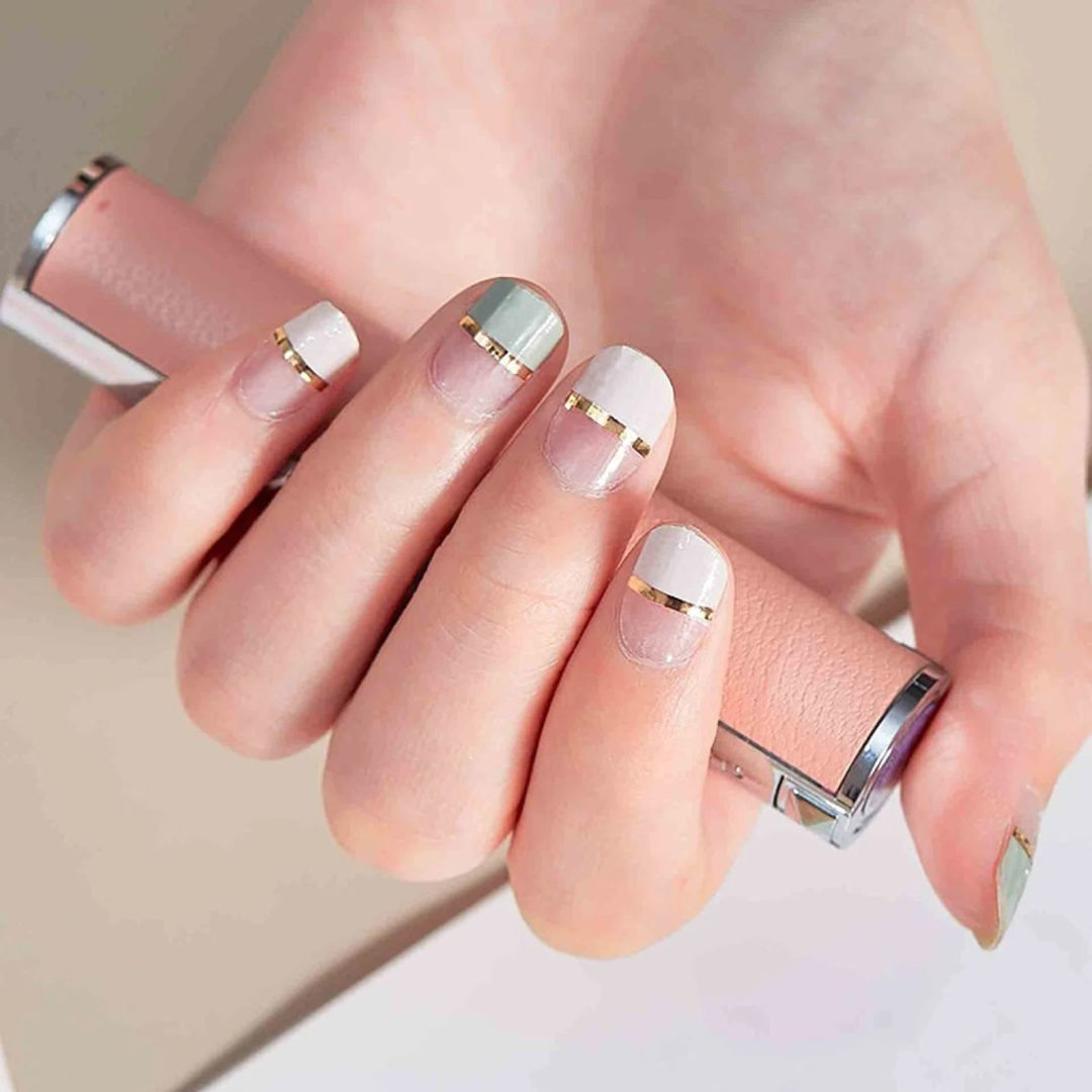 White and sage green nails with gold strips