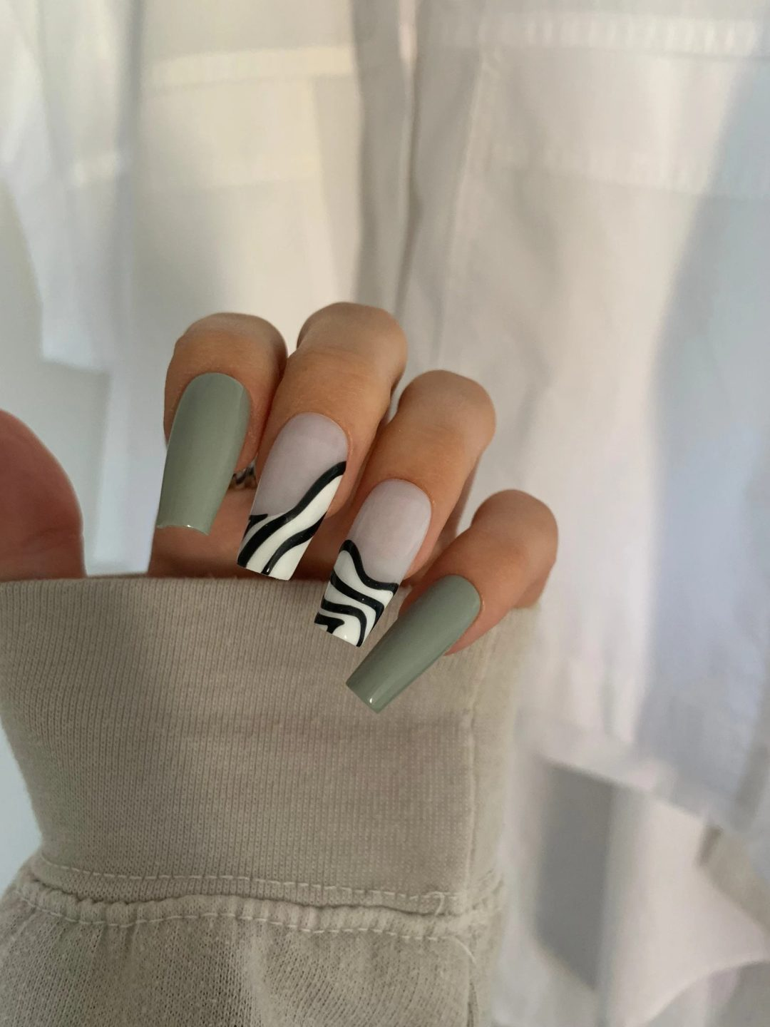 Matte sage green nails with black and white swirls