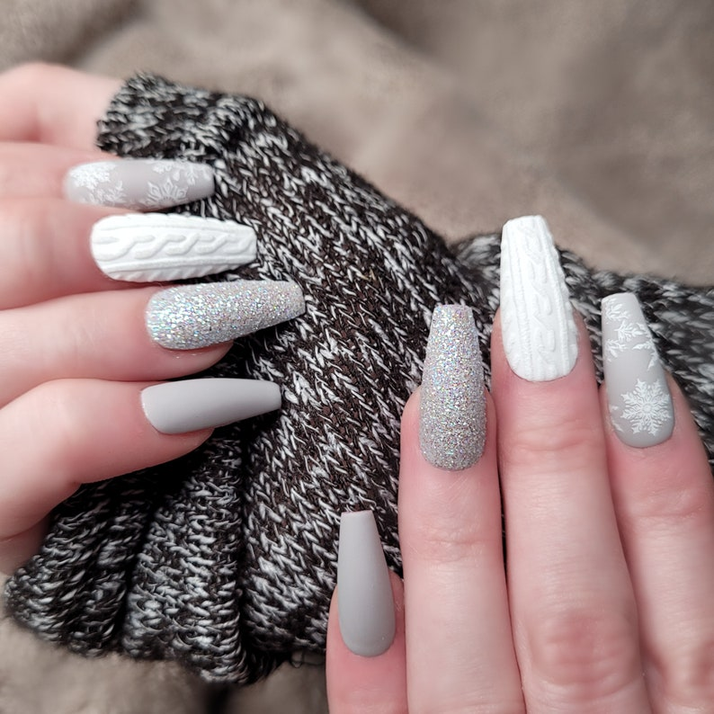 Light grey and white sweater nails with glitter and snowflakes