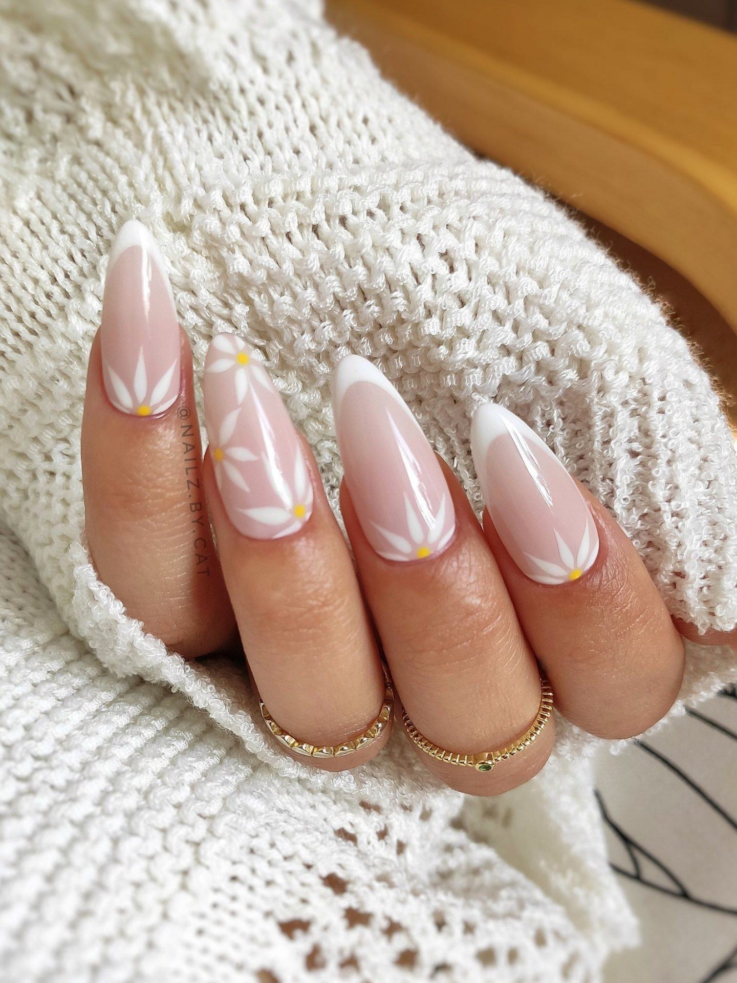 Beautiful almond French tip nails with daisy nail art