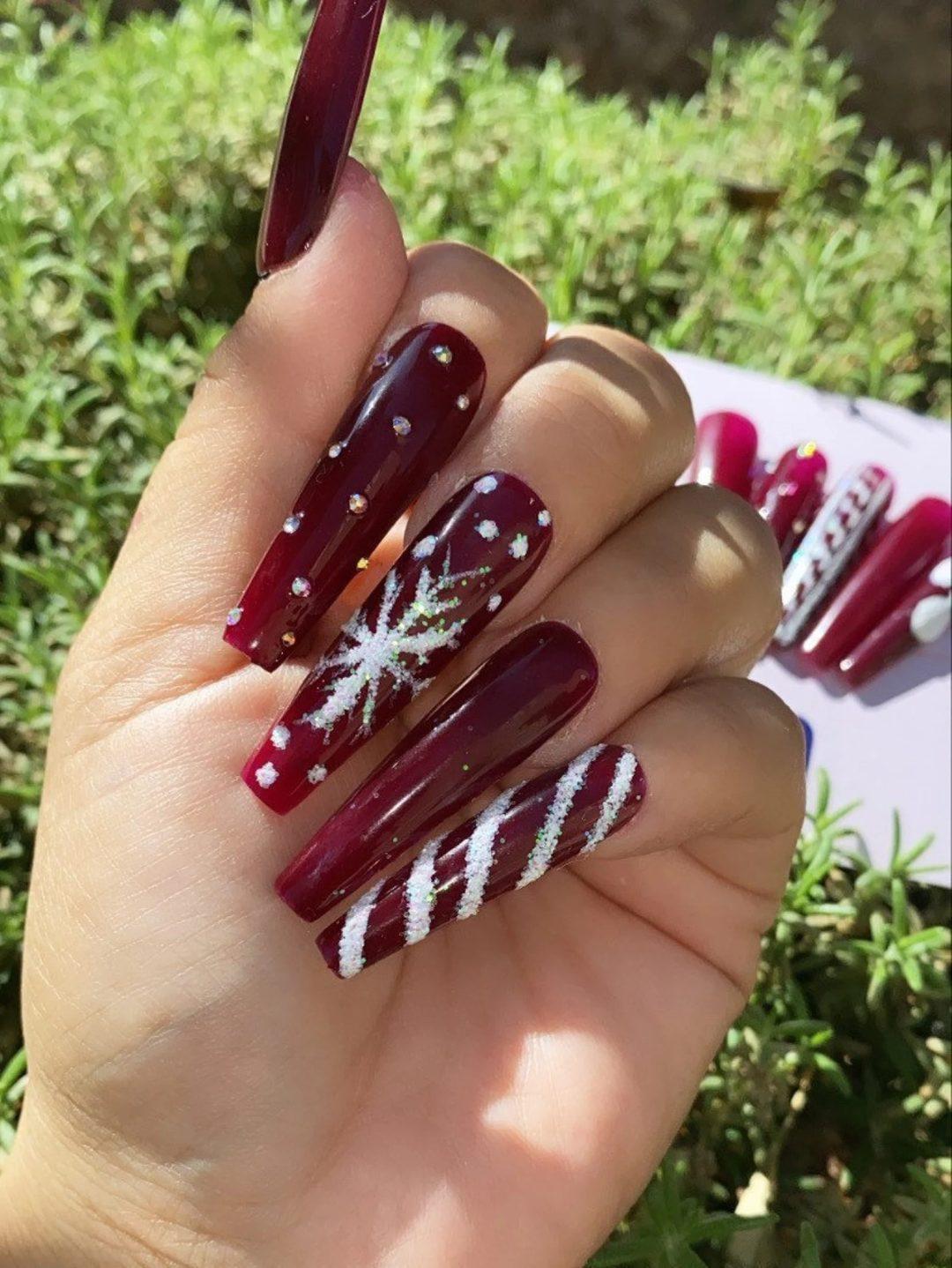 Maroon and white snowflake nails
