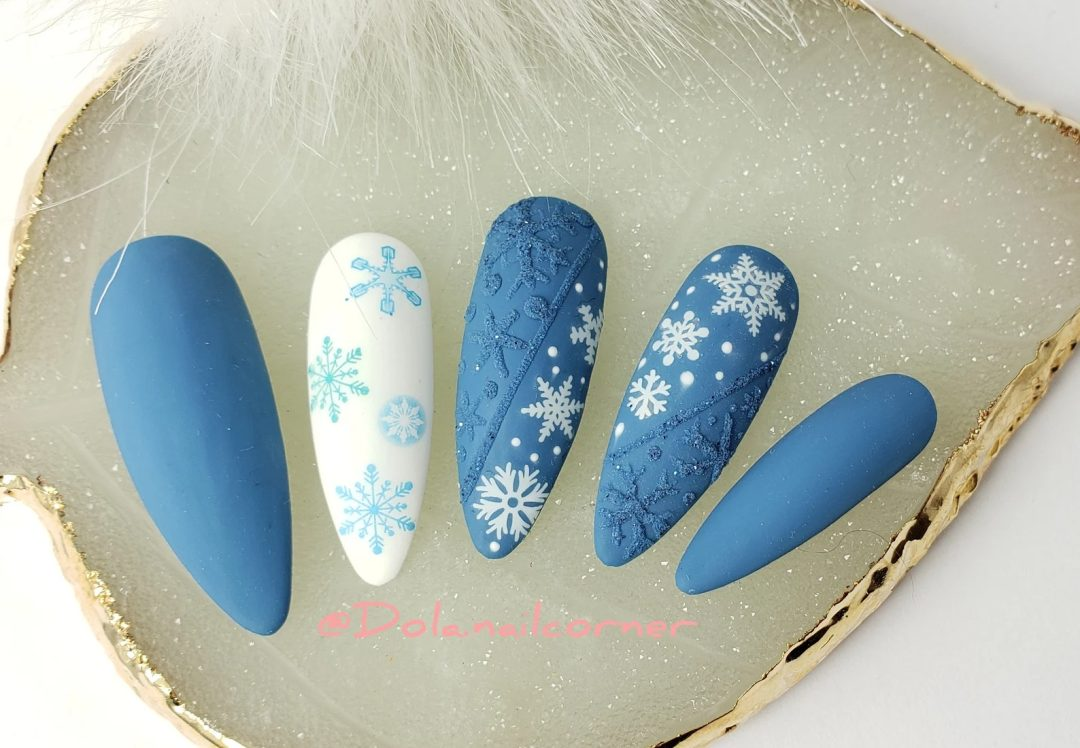 Matte blue and white snowflake nails