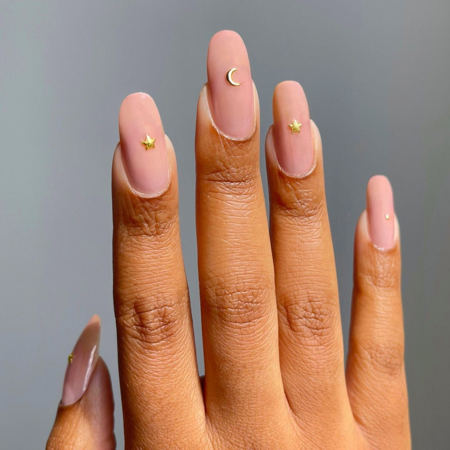 Nude nails with gold celestial stars and moon nail art