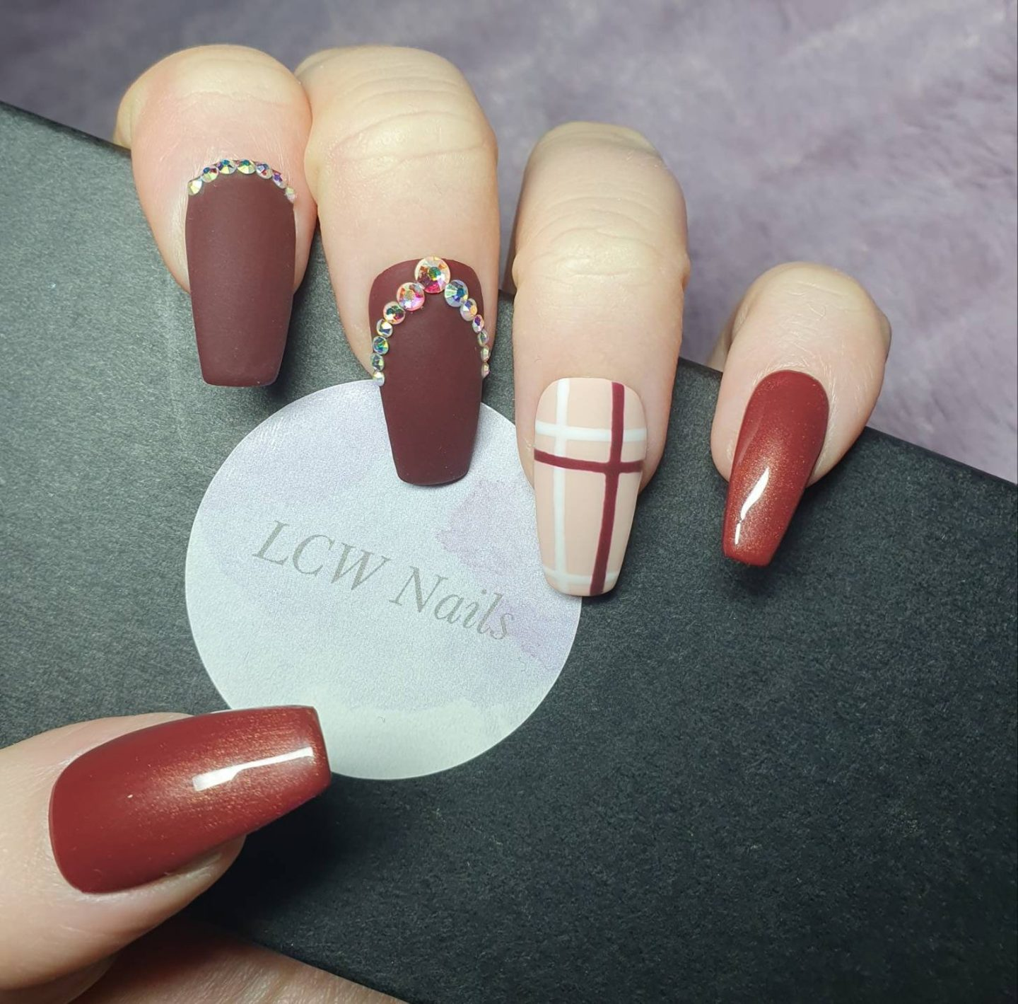 Matte burgundy Burberry inspired plaid nails with rhinestones