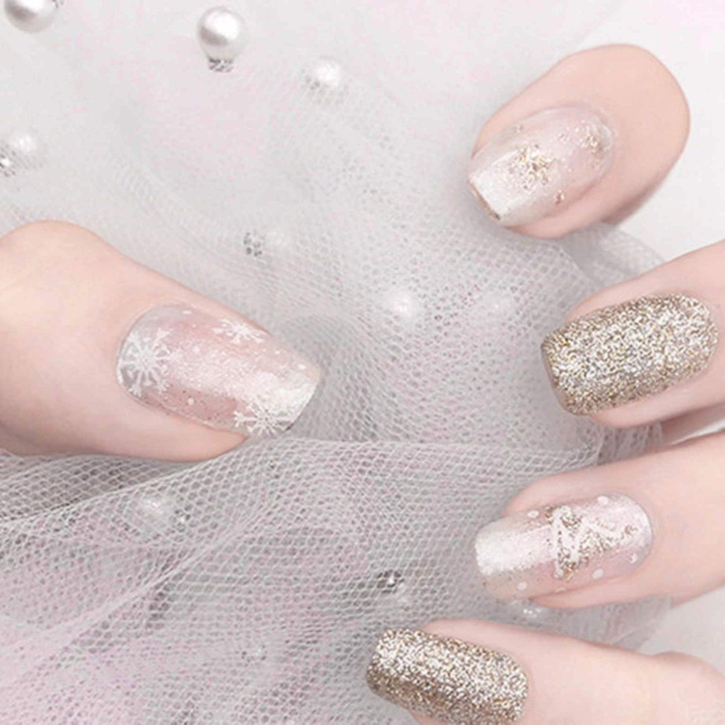 Cute short and white snowflake nails with gold glitter
