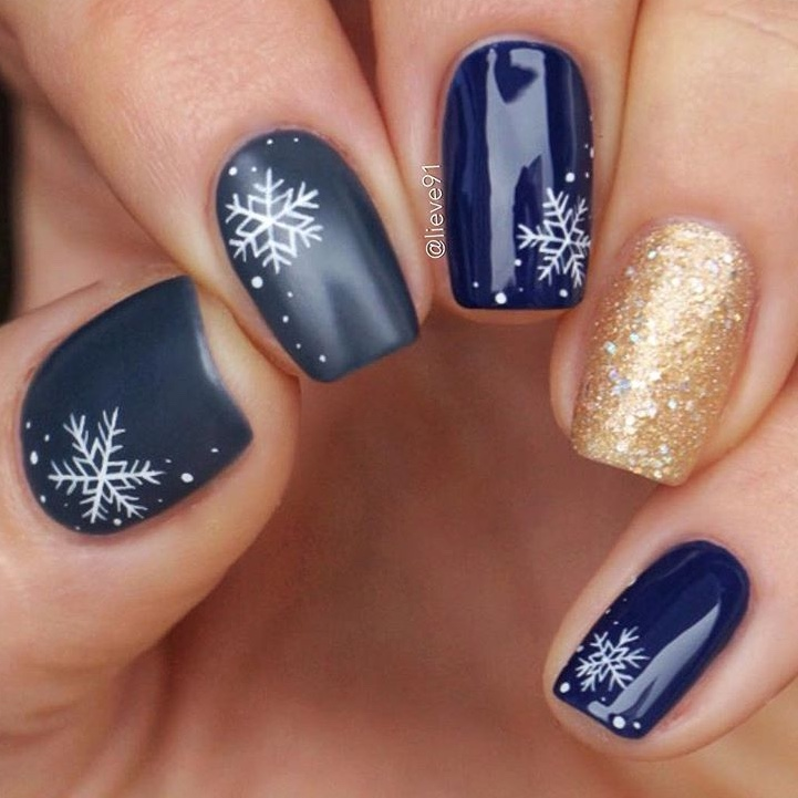 Short navy blue snowflake nails with gold glitter