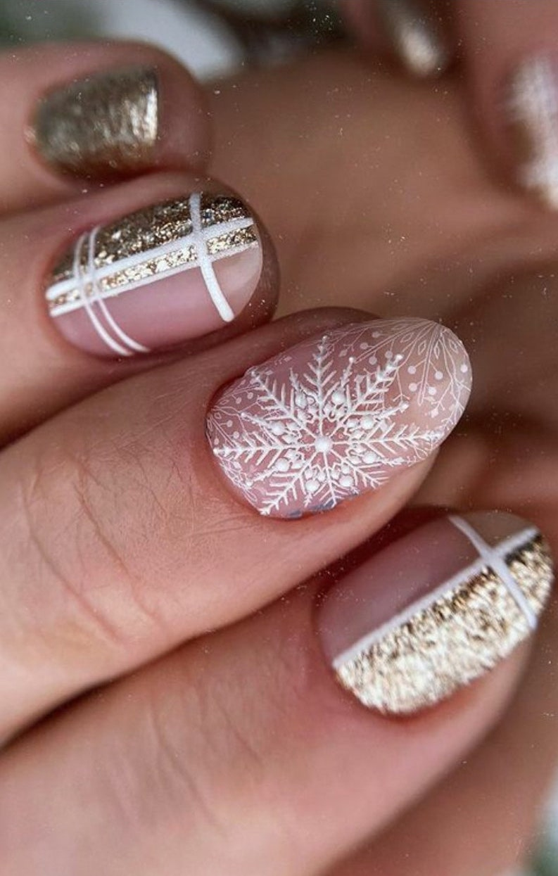 Cute short white snowflake nails with gold glitter